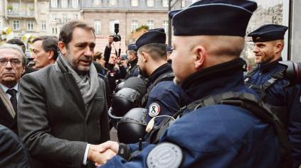 French Interior Minister Christophe Castaner (L) greets officers during the reopening of the christmas market of Strasbourg, eastern France, on December 14, 2018 as the author of the attack was killed on December 13, 2018. - The Chrismas market closed as three people were killed and 13 wounded when a lone gunman, identified as Cherif Chekatt, 29, opened fire on shoppers on December 11, 2018. (Photo by SEBASTIEN BOZON / AFP)
