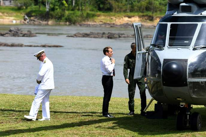 French President Emmanuel Macron adjusts his tie upon his arrival for a visit in Maripasoula, part of his trip to French Guiana